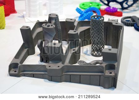 Objects printed on metal 3d printer and printer that prints plastic close-up. A model created in a laser sintering machine close-up. DMLS, SLM, SLS, FDM technology. Modern additive technology.