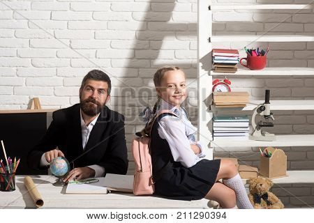 Back to school and first school day concept. Family sits by desk with school supplies. Schoolgirl and her dad with satisfied faces wearing bag. Girl and father in classroom on white brick background