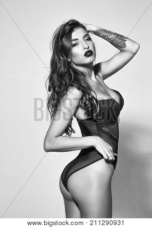 pretty woman or cute sexy girl in erotic black bodysuit with long curly brunette hair has red lips on adorable face and tattoo on hand on grey background
