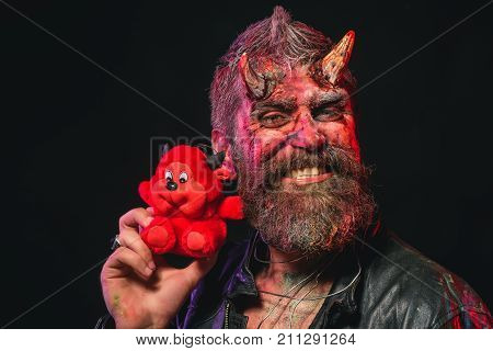 Halloween Man Smile With Red Devil Toy On Black Background