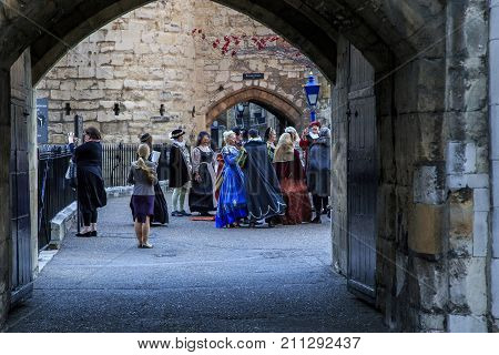 LONDON, GREAT BRITAIN - SEPTEMBER 21, 2014: Unidentified visitors are preparing for a costumed excursion to the night Tower of London.