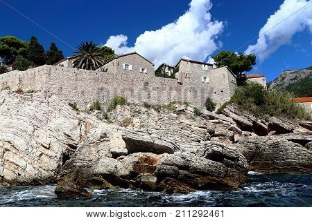 SVETI STEFAN, MONTENEGRO - SEPTEMBER 14, 2013: This is the view from the sea of the fragment of the building of the impregnable rocky island.