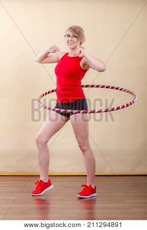 Fitness sport training and healthy lifestyle. Young woman in full length doing exercise with hula hoop girl having fun playing game hula-hoop