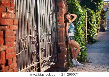 Fashionable young woman in a sexy denim shorts. sexy brunette girl with sporty body wearing jeans shorts. summer young brunette woman with long curly hair, in jeans short. Place for text