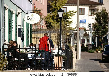 NIEDER-OLM, GERMANY - OCTOBER 14: Visitors of the Café Blums are sitting in the sunshine outside on a veranda on October 14, 2017 in Nieder-Olm.