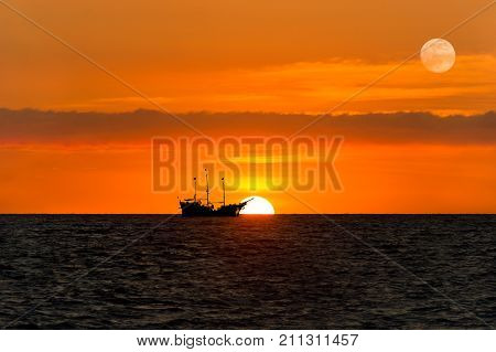 Ship pirate silhouette is a pirate ship sitting at sea watching the ocean sunset as the moon rises in the sky.