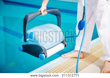 Swimming Pool Cleaner. Pool Cleaning Machine and the Caucasian Worker.