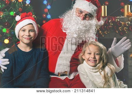 Wishes list to Santa's ear. Kids around the Santa Claus tell him they wishes at Christmas eve. Family, good father.
