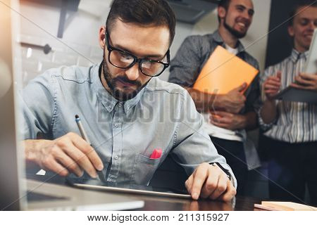 Bearded Glasses Manager Analyzes Earnings Of Shares On Tablet Screen. Architect Draws Project With S