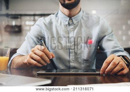 Male Hands Of A Businessman Closeup Working On A Tablet With A Stylus. Young Bearded Student Typing