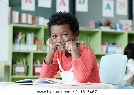 African boy sitting at his desk with smiling face in pre-elementary classroom kindergarten pre school education concept