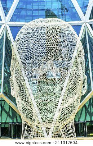 CALGARY, ALBERTA, CANADA - AUGUST 9, 2017 Wire Head Wonderland Public Sculpture Bow Building Calgary Alberta Canada. Sculpture created by Spanish Sculptor Jaume Piensa in 2013.
