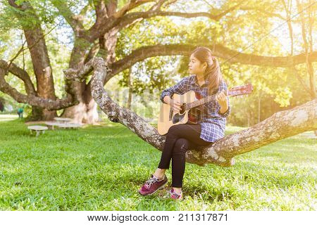 Female fingers playing guitar outdoor in summer park. Musician woman and her guitar in nature park Practice guitar. playing guitar. playing guitar park. playing guitar classic. playing guitar chord. playing guitar wood. playing guitar woman