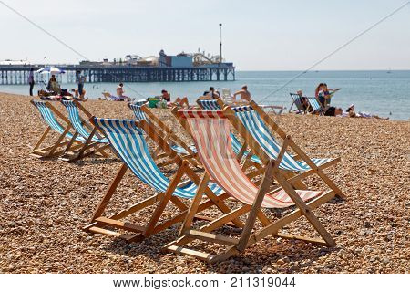 BRIGHTON GREAT BRITAIN - JUN 17 2017: Classic deckchairs and people sunbathing on the pebble beach at the Brighton pier a warm sunny day. June 17 2017 in Brighton Great Britain