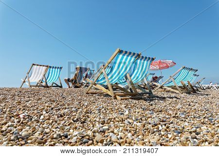 BRIGHTON GREAT BRITAIN - JUN 17 2017: Classic deckchairs and people sunbathing on the pebble beach. Blue sky and sunny. No people and blue sky. June 17 2017 in Brighton Great Britain