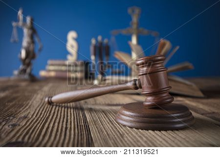 Judge concept. Mallet of the judge, justice scale and books on wooden desk and blue background.