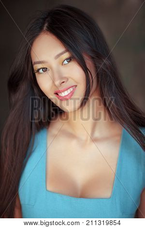 Woman smiling. Portrait of happy lovely and beautiful mixed race asian caucasian young girl outdoor against gray blurred bokeh background. Gorgeous fashion model looking at camera.