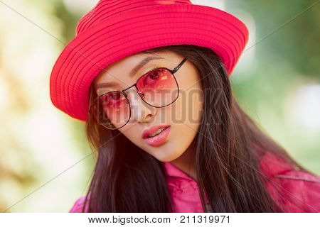 Asian woman fashion close-up portrait. Beautiful mixed race asian caucasian young girl in pink hat jaket and red sunglasses looking at camera outdoor against green blurred bokeh nature background. Gorgeous slim model in trendy casual colourful clothes pos