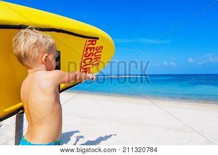 Life saving yellow board with surf rescue sign. Funny children lifeguard stand on duty look at blue sea. Assure swimming people safety. Summer family vacation on ocean beach. Travel background.