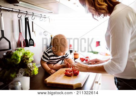 Unrecognizable young mother with a baby son doing housework. Beautiful woman and baby boy cooking in the kitchen.