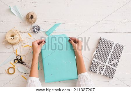 Closeup of woman's hands with gift ribbon twine tape and present wrapped in turquoise gift paper on white wooden background. Christmas birthday or any other celebration preparations.