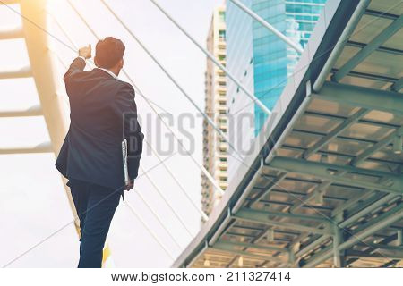 Businessman look to target in city outdoor on building background hand holding laptop computer. image processing instagram color.