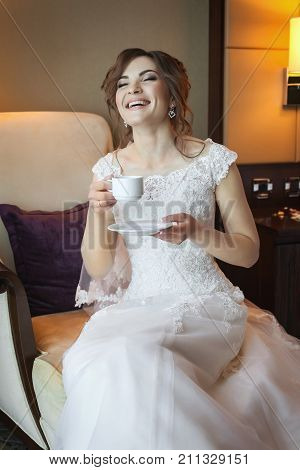 Attractive young bride preparing for wedding in the morning, drinking coffee, laughting and waiting for the groom