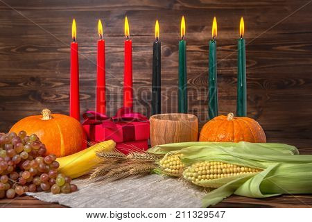 Kwanzaa Festival Concept With Seven Candles Red, Black And Green, Gift Box, Pumpkins, Ears Of Wheat,