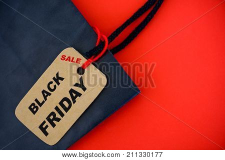 Shopper with Black Friday paperbag and ticket label sale tag on red blackground.
