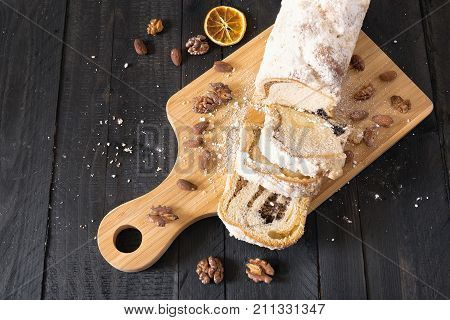 High angle view of a delicious pound cake sliced on a trencher filled with poppy and nuts surrounded by roasted walnuts and almonds on a wooden table.