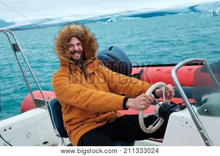Happy man on a boat on the icy lagoon of Joculsarlon, Iceland. Famous icelandic ice lagoon, where ice goes downhill to reach ocean. People walking and taking boat to investigate famous destination.