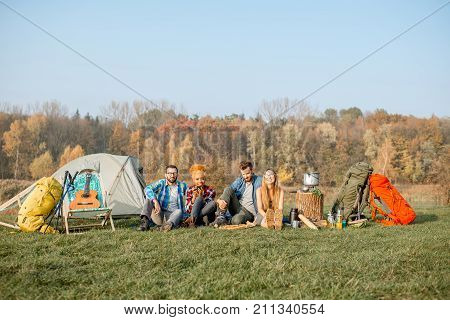 Multi ethnic group of friends having a picnic, eating pizza, sitting in a row at the camping with tent and hiking equipment near the forest
