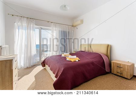 Modern master bed. comfortable beds including designs, walls are white color, sea view, inside rooms of a apartment.