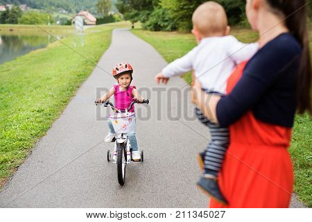 Cute little happy girl with her mother and younger toddler brother in the nature by the lake. Girl is cycling and smilling. Slow motion.