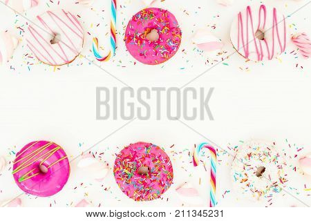 Frame of colorful pink donuts with marshmallow and sugar cane on white background. Flat lay, top view
