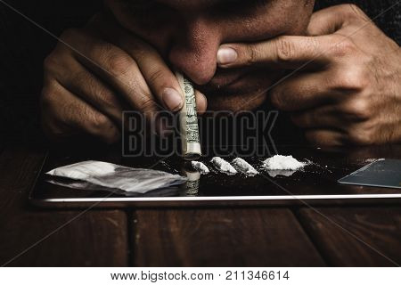 Drug abuse, man taking drugs, snorting lines of cocaine powder, close up, toned
