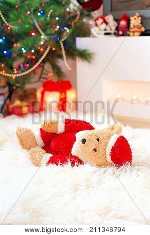 Forgotten gift. Santa teddy bear toy lie on sheepskin rug near illuminated christmas tree. Multicolored indoors vertical image.