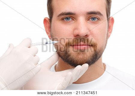 A male doctor is injected by a doctor wearing white gloves, botox on the cheek near the mouth. Photo on white background