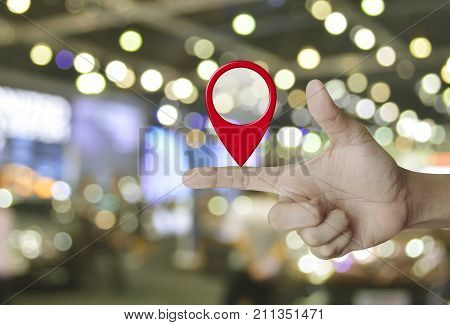 Map pin location button on finger over blur light and shadow of shopping mall Map pointer navigation concept
