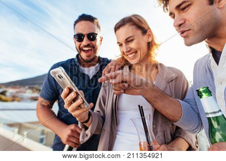 Group Of Friends Having Fun With Smartphone At Party