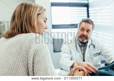 Woman explaining about her health while doctor listening. Female patient talking with doctor during a consultation in clinic.