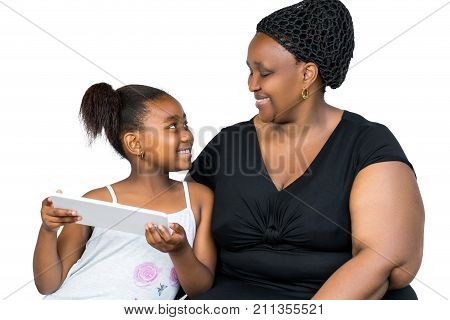 Close up portrait of little african girl and mother having fun together with digital tablet isolated on white background.Mother and daughter looking at each other.