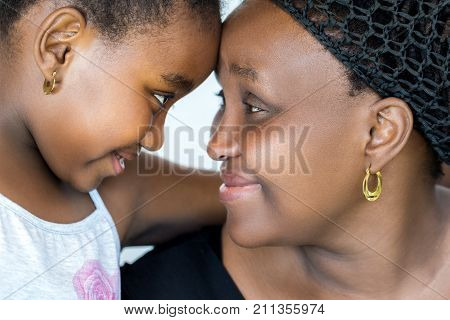 Close up face shot of african mother and little daughter joining heads. Mother and child showing affection isolated on white background.