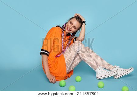 Cheerful girl in dress laughing with eyes closed while sitting on blue background with tennis balls around.
