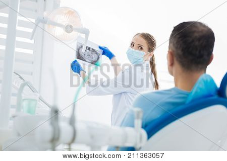Medical diagnosis. Nice pleasant female doctor holding an Xray scan and looking at it while putting the diagnosis