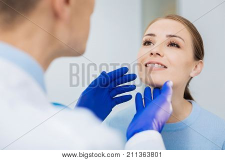 Visit to the dentist. Nice positive young woman holding her chin up and smiling while being checked by a dentist