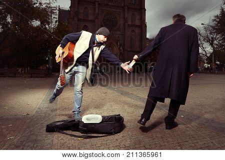 Unknown man stealing money to a beggar with guitar