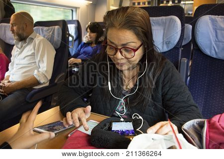Asian Thai Old Woman Playing Moblie Phone And Listen Music While Sit On Train Running From France Go