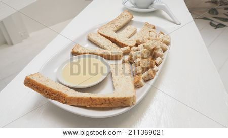 Love breakfast create idea from whole wheat bread and sweetened condensed milk serve with Tofu green tea milk in ceramic white cup isolate on wood chair has copy space.