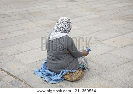 Old Woman Beggar Sitting Begging Money From  French People And Foreigner Travlers At Walkway For Go